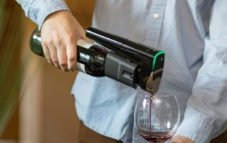 Coravin wine preservation device in hand used to pour red wine